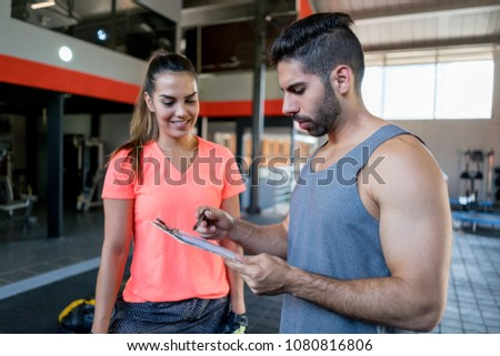 Fitness instructor checking the training program for her client while she is standing next to him smiling very happy