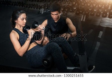 Fitness instructor exercising with his client at the gym, Personal trainer helping woman working with heavy dumbbells