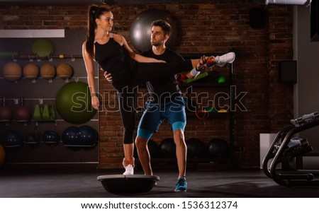 Fitness instructor supervising and helping the female athlete in gym exercise with balancing flipped bosu ball, instability high-intensity interval training (HIIT) on an unstable platform
