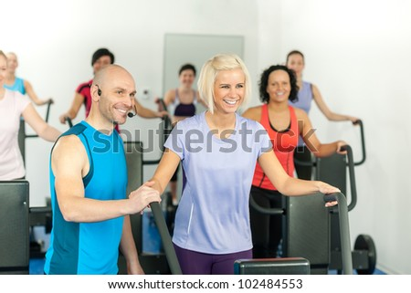Fitness instructor with gym people exercise on cross-trainer