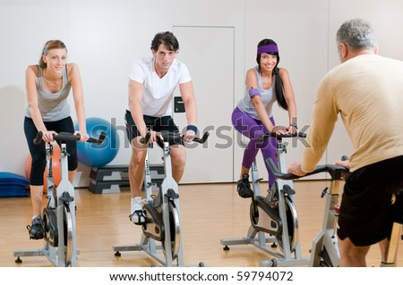 Fitness instructor with his class of cycler at gym