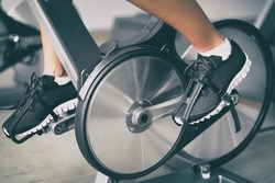 Fitness machine at home woman biking on indoor cycling stationary bike exercise indoors for cardio workout. Closeup of shoes on bicycle.