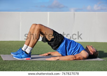 Fitness man doing bodyweight glute floor bridge pose yoga exercise. Fit athlete exercising glutes muscles with butt raise at summer outdoor gym instruction class on grass.