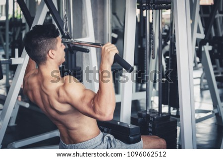 Fitness man doing exercise with machine in sport gym, healthy lifestyle concept