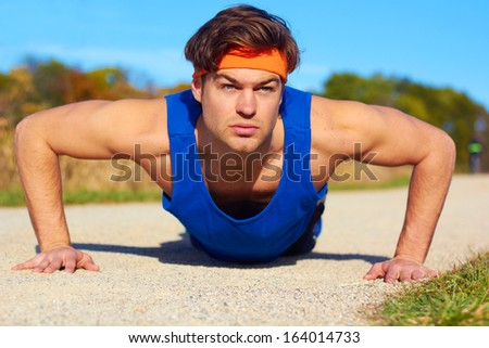 Fitness man doing push ups in nature. Color image, copy space, handsome young man doing push ups for exercise in the grass.Horizontal