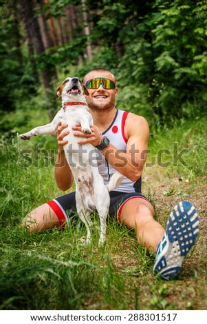 Fitness man in sportswear with his dog in the forest.