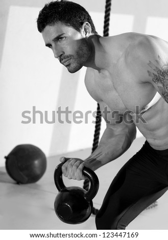 Fitness man lifting kettlebell workout exercise at gym