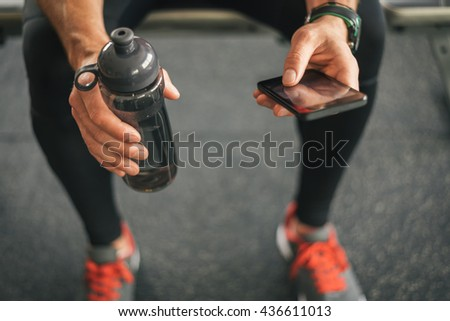 Fitness man looking to the phone for motivation before gym workout. Sporty male athlete looking his smartphone holding water bottle.