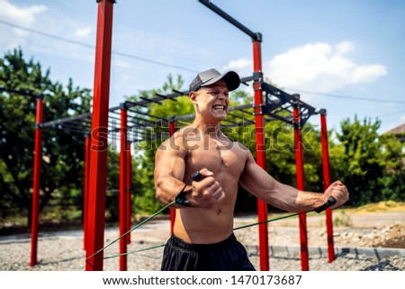 Fitness man training chest with resistance bands at street gym yard. Strength and motivation. Outdoor workout.Body workout with equipment outside. Elastic rubber band accessory.