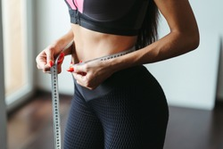 Fitness motivation and successful weight loss. Woman with perfect slim body measuring her waistline with tape, close up. Diet, home training, healthy lifestyle concept