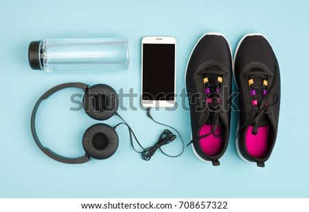 Fitness objects isolated on blue background. Sneakers, water and audioplayer #708657322