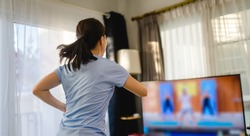 Fitness online Stay home.home fitness workout class live streaming online.Asian woman doing strength training cardio aerobic run exercises.Watching videos on a smart tv in the living room at home.