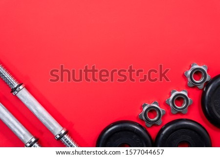 Fitness or bodybuilding. Sports equipment on a red background: dumbbells, barbells, top view with plenty of copy space