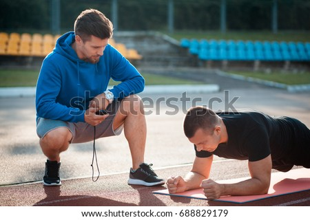 fitness outdoor workout with trainer; morning plank exercises with personal coach with stopwatch;