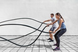 Fitness people exercising with battle ropes at gym. Woman and man couple training together doing battling rope workout working out arms and cardio for cross fit exercises.