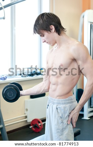 Fitness - powerful muscular man lifting weights in gym club