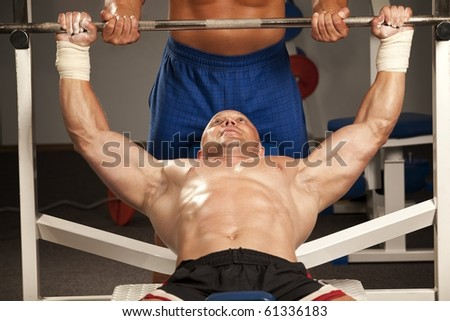 Fitness - powerful muscular man with a bar weights in hands training