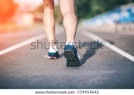 Fitness Runner feet on track focus on sport shoe. Urban Jogger running Getting ready to start