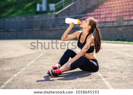 Fitness runner woman drinking water or energy drink of a sport bottle. Athlete girl doing exercises on the training at stadium. Healthy active lifestyle. #1018645192