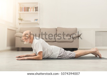 Fitness, senior man training yoga in cobra pose at home. Active lifestyle and healthcare in any age, copy space