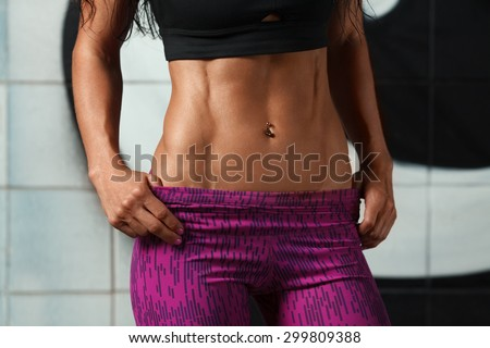 Fitness sexy woman showing abs and flat belly. Beautiful muscular girl, shaped abdominal, slim waist