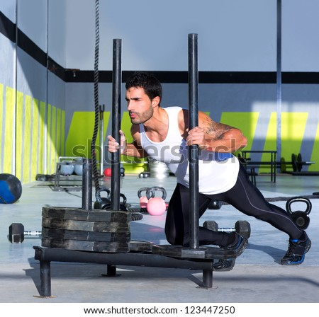 Fitness sled push man pushing weights workout exercise