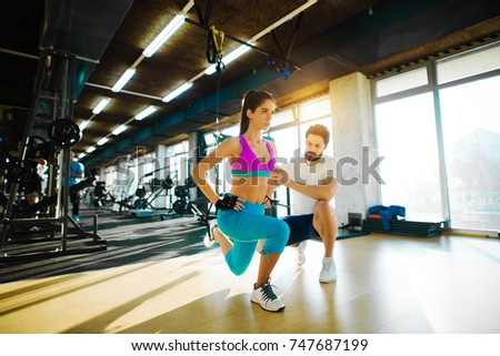 Fitness slim girl doing one leg stretching with rope from top and help from a personal trainer in the gym.