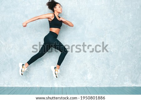Fitness smiling black woman in sports clothing with afro curls hairstyle.She wearing sportswear. Young beautiful model with perfect tanned body.Female jumping and running in studio near gray wall Stock photo ©
