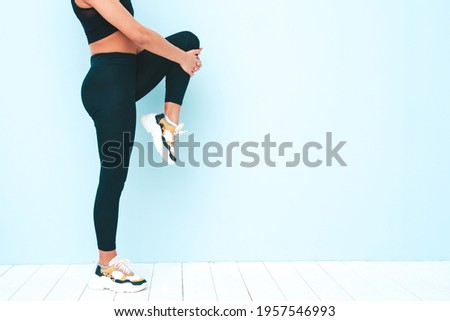 Fitness smiling black woman in sports clothing with afro curls hairstyle.She wearing sportswear.Young model stretching out legs before training.Female sitting in studio near blue wall. No face Stock photo ©