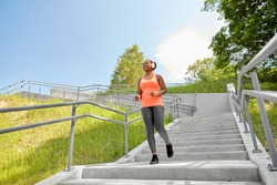 fitness, sport and healthy lifestyle concept - happy smiling young african american woman in headphones downstairs at park