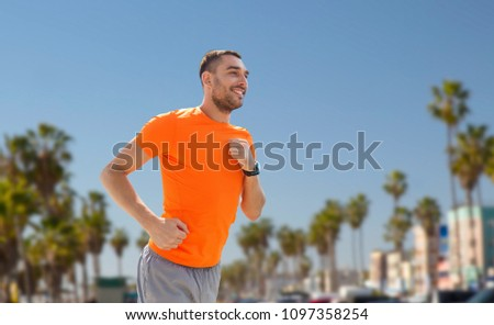 fitness, sport and healthy lifestyle concept - smiling young man with heart rate watch running over venice beach background in california