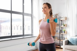fitness, sport and healthy lifestyle concept - smiling young woman with dumbbells exercising at home