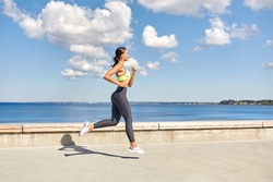 fitness, sport and healthy lifestyle concept - young woman running along sea promenade