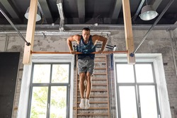 fitness, sport and lifestyle concept - young man exercising on horizontal bar in gym