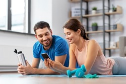 fitness, sport and technology concept - happy couple with smartphone having break at home