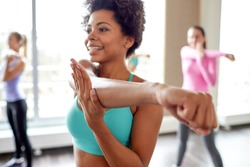 fitness, sport, dance, people  and lifestyle concept - close up of smiling african american woman with group of women dancing zumba in gym or studio