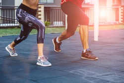 fitness, sport, exercise, lifestyle concept. close up of legs man and woman doing exercise on street sports ground. Team of two athletes exercising lunges while having sports training in the morning.