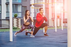 fitness, sport, exercise, lifestyle concept. Mixed race young man and woman doing exercise on street sports ground. Team of two athletes exercising lunges while having sports training in the morning.