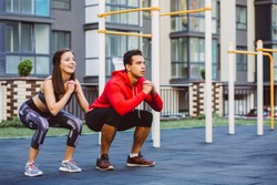 fitness, sport, exercise, training and lifestyle concept - mixed race young man and woman doing squatting exercise on street sports ground. Staying fit and healthy concept