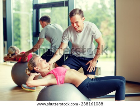 Stock Photo fitness, sport, exercising and diet concept - smiling young woman and personal trainer in gym