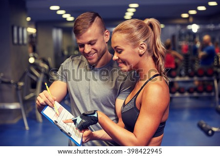 fitness, sport, exercising and diet concept - smiling young woman with personal trainer and exercise plan on clipboard in gym