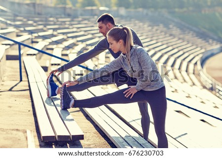 fitness, sport, exercising and lifestyle concept - couple stretching leg on stands of stadium Stock photo ©