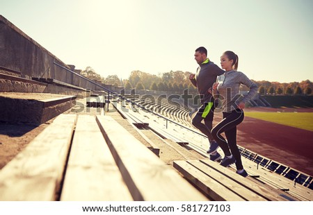 fitness, sport, exercising and lifestyle concept - happy couple running upstairs on stadium