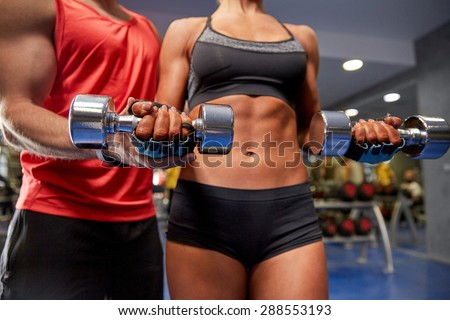 fitness, sport, exercising and weightlifting concept - young woman and personal trainer with dumbbells flexing muscles in gym