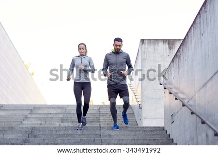 fitness, sport, exercising, people and lifestyle concept - couple walking downstairs on stadium #343491992