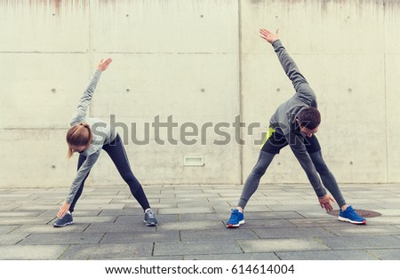 fitness, sport, exercising, training and people concept - couple stretching on city street #614614004