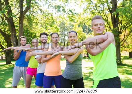 fitness, sport, friendship and healthy lifestyle concept - group of happy teenage friends or sportsmen exercising and stretching hands at boot camp - Shutterstock ID 324776699