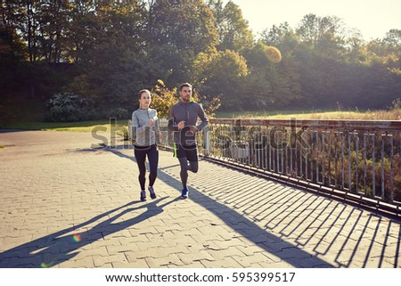 fitness, sport, friendship and lifestyle concept - happy couple running outdoors #595399517