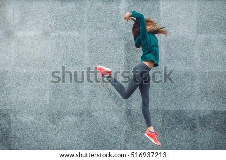 Shutterstock Fitness sport girl in fashion sportswear dancing hip hop in the street, outdoor sports, urban style