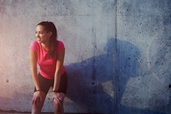 Fitness sport girl resting after intensive evening run, young attractive runner taking break after jogging outdoors, female jogger in bright sportswear smiling looking away, advertising for sports
